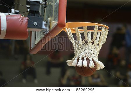 Ball passing through the arch of a basketball hoop during match