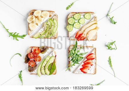 healthy breakfast with sandwiches set on white table background top view