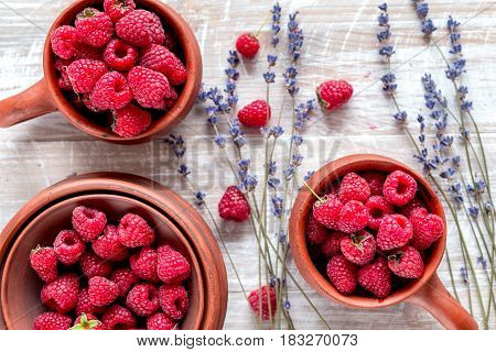 raspberry in pottery and lavender flowers on rustic desk background top view