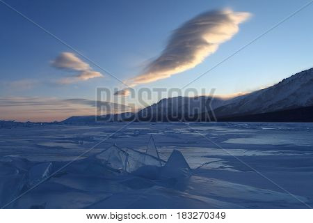 Beautiful figured clouds over blue ice formations and snowcapped mountains on sunset