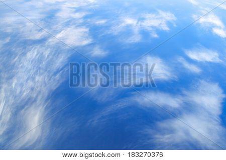 Light fluffy clouds on blue sky background