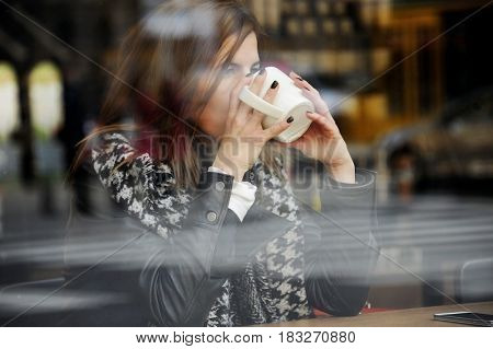 trendy woman sitting in a cafeteria and using her mobile phone. Busy woman in a coffee shop viewed through glass with reflections as she is siting at a table and drink a coffee.