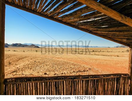 View from wooden cabin to grassland desert savanna plain and mountain range. Shelter provides protection against big game wild animals. Namibia, Africa.