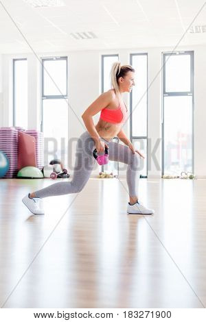 Fit woman doing lunge exercise with a kettlebell. Workout and healthy lifestyle concept.