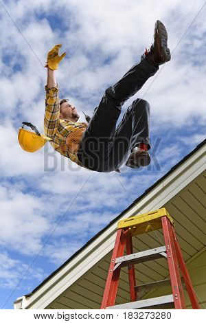 Man falling from edge of roof while using ladder