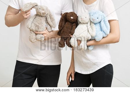 Couple in white T-shirts and black pants in the studio on the light background. They are holding plush multicolored rabbit toys. Closeup. Horizontal.