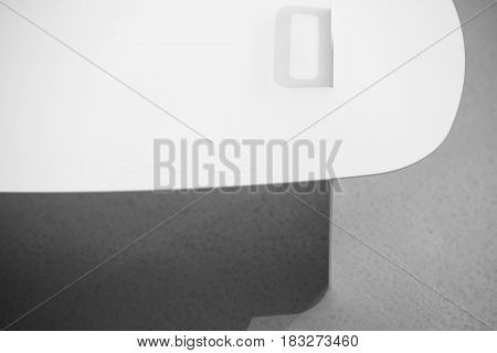 White metal stand on the gray surface. It drops shadows on the left side. Closeup low aperture photo. Indoors. Horizontal.