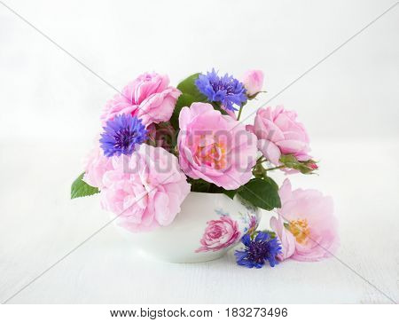 Colorful bouquet of light pink roses and cornflowers on pale  grey  background.