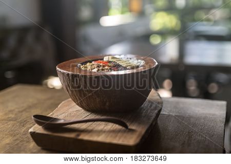 Wooden table with a board with a spoon and a plate made from a coconut on the blurry background. In the plate there are slices of banana and strawberry with nuts and seeds, pieces of coconut. Closeup.