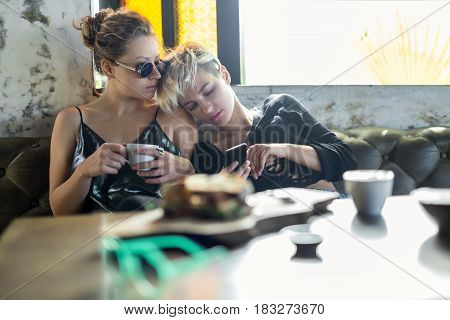 Sexy girls on the sofa on the window background in the cafe. One girl leans on the shoulder of other and looks at the cellphone. Second girl in sunglasses holds a cup and looks to the side.