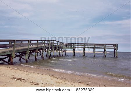 A wood pier on the sand and going into the Bay