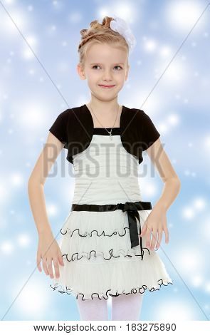 Beautiful little blonde girl dressed in a white short dress with black sleeves and a black belt.Girl poses for the camera.Blue Christmas festive background with white snowflakes.