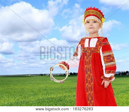 Cheerful little girl in Russian folk dress. The girl hits the drum.On the background of green grass and blue sky with clouds.