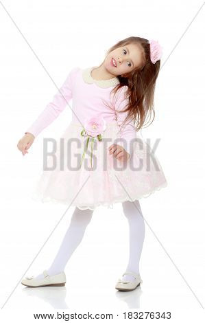 Dressy little girl long blonde hair, beautiful pink dress and a rose in her hair.Isolated on white background.