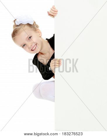 Beautiful little blonde girl dressed in a white short dress with black sleeves and a black belt.The girl peeks out from behind white banner.