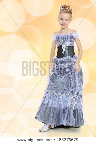 Slender little girl , with beautiful hair on his head, elegant long Princess dress.Girl holding hands to the edge of the dress and put forward a foot to show the shoes.