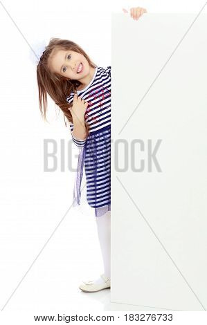 The little blonde girl with long hair and with a white bow on her head , in a blue striped summer dress.She peeks out from behind white banner.Isolated on white background.