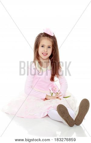 Dressy little girl long blonde hair, beautiful pink dress and a rose in her hair.She sits on the floor stretching the legs forward.Isolated on white background.