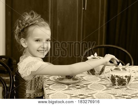 Beautiful little girl Princess , sitting at an antique table with a lace tablecloth and drinking tea.Black-and-white photo. Retro style.