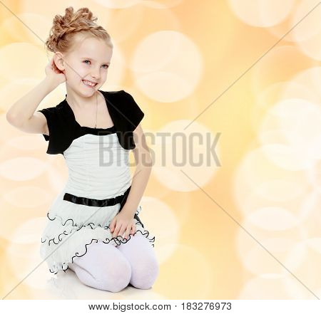 Beautiful little blonde girl dressed in a white short dress with black sleeves and a black belt.Girl stands on her knees and straightens her arm hair .