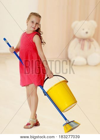 Beautiful little girl in a red short dress with a bucket and brush pleasure to cleans the house.In the children's room in which sits a Teddy bear.