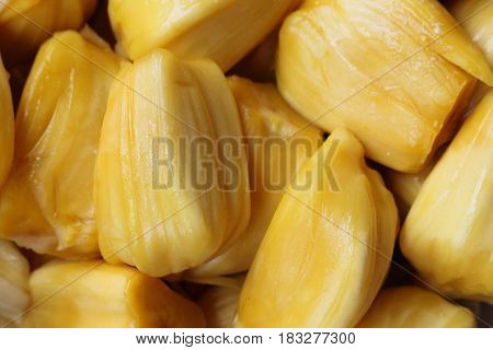Many yellow jackfruit are in a white plate.