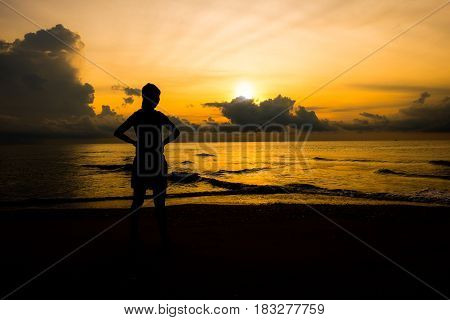 Silhouette of young sport women looking up sunrise or sunset at the beach that meaning the power of life and positive thinking.