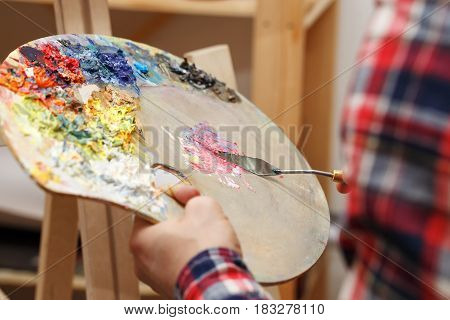 Man mixes oil paints with a palette knife on a wooden palette in an art school. Courses of drawing for adults.