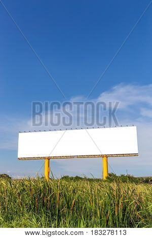 Outdoors blank billboard ready for new advertisement with nature scene and blue sky background.