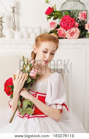 Sweet ballerina in a stage costume holds a bouquet of spring flowers. Retro dress. A gift from a fan.