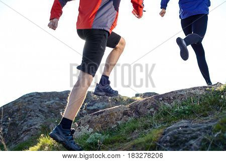 Young Couple Running on the Rocky Trail in the Mountains in the Morning. Active Lifestyle Concept