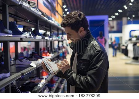 young male customer choosing white sneakers at supermarket store