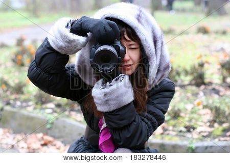A young girl is holding a camera. Photojournalist makes photos