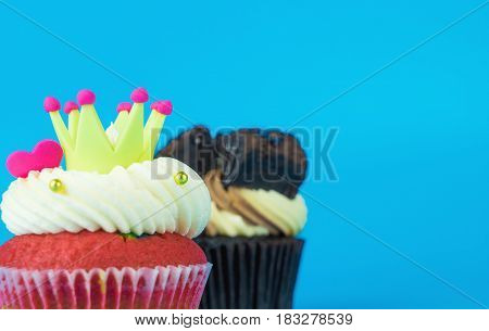 Rainbow heart crown and chocolate cupcake with Blue copy space