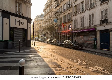 Paris, France, March 27, 2017: View on narrow cobbled street among traditional parisian buildings in Paris, France.