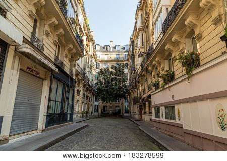 Paris, France, March 26, 2017: View on narrow cobbled street among traditional parisian buildings in Paris, France.