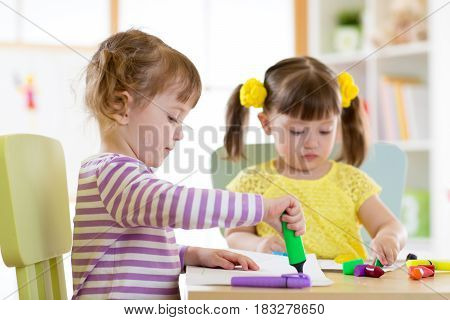 Two beautiful children girls drawing in kindergarten or preschool.