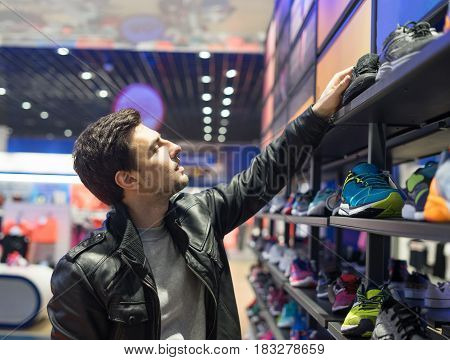 portrait of young male customer choosing sneakers at supermarket store. He is taking shoes from she shelf.