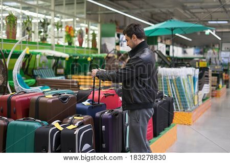 male customer choosing travel suitcase in the supermarket