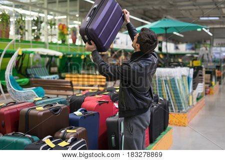 male customer choosing travel suitcase in the supermarket. He picked up the bag.