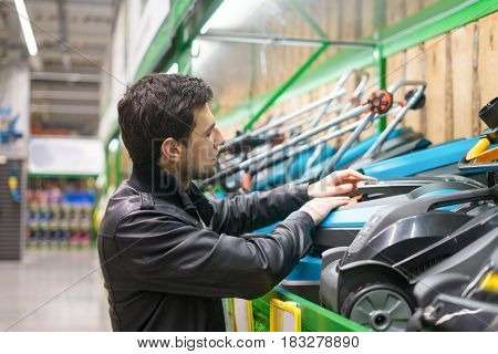 portrait of male customer choosing lawnmower in supermarket