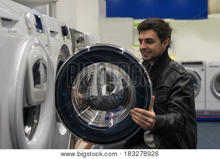 portrait of male customer choosing washer in supermarket store. He opened washing machine cover