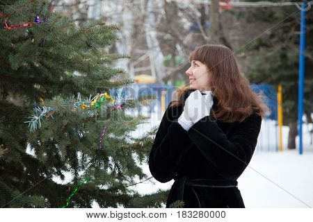 Young woman expresses emotions. The girl is walking in the park, admiring the fir
