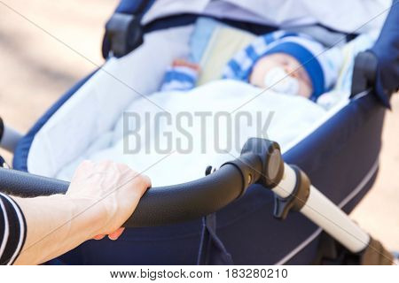 Hand Of Woman Holding Babies Pram With Newborn Baby Sleeping Inside