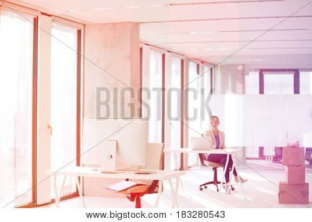 Computer monitor on desk with businesswoman working in background at office