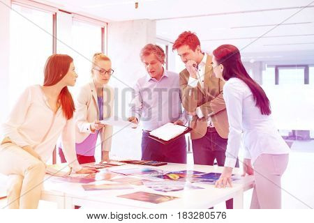 Mature businessman with team working on new project at office