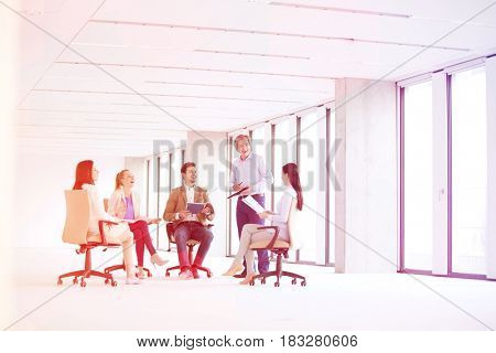 Mature businessman discussing with colleagues on chair in empty office