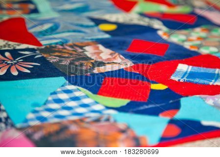 An old patchwork quilt. Multicolored pieces of fabric are sewn together,