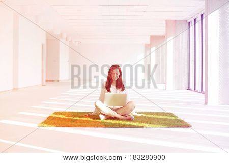 Young businesswoman with laptop while sitting on grass carpet in empty office