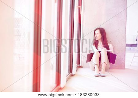 Young businesswoman with file looking through office window while sitting on floor